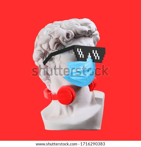 Statue. Earphone on a red background. Gypsum statue of David's head. Creative. Plaster statue of David's head in sunglasses and medical mask. Minimal concept art.