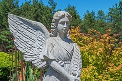 Statue grieving angel with wings against green trees and blue sky. Death, loss, condolence concept