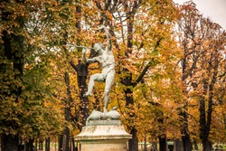 Statue in alley of Luxembourg Gardens, Jardin du Luxembourg in Paris France, covered with orange autumn leaves on an Autumn day, Paris in the Fall