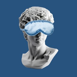 Statue in blue sleep mask. Gypsum statue of David head. Plaster copy of David's head in sleeping mask. Creative, sleep and relax concept. Minimal concept art. Last or blind judgment.
