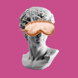 Statue in gold sleep mask. Gypsum statue of David head. Plaster copy of David's head in sleeping mask. Creative, sleep and relax concept. Minimal concept art. Last or blind judgment.