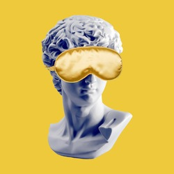 Statue in gold sleep mask. Gypsum statue of David head. Plaster copy of David's head in sleeping mask. Creative, sleep and relax concept. Minimal concept art. Last or blind judgment. Toned picture
