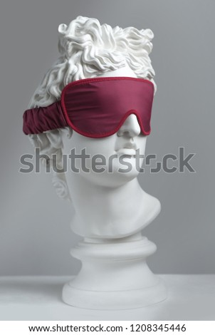 Statue. Isolated. Red sleeping mask.  Gypsum statue of Apollo's head. Man. Statue. Plaster statue of Apollo's in red sleep mask.