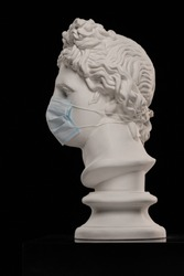 Statue of a bust of Apollo's head in a disposable protective medical mask covering his face
