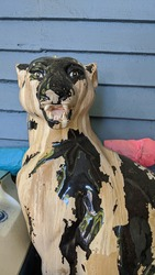statue of a ceramic black panther with peeling paint