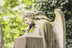 Statue of a contemplative angel. Olsany Cemetery, the largest graveyard in Prague, Czech Republic. Summer time