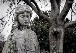 Statue of a graceful angel mourning over a grave in a London cemetery surrounded by trees