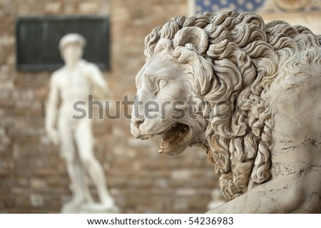 Statue of a lion at the Loggia dei Lanzi in Piazza della Signoria in Florence Tuscany. Michelangelo's David statue in front of the Palazzo Vecchio background