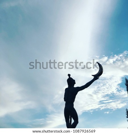 Statue Of A Man Catching The Moon 1087926569