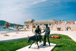 Statue of a man with a woman on a donkey near the Zora hotel, Primosten town, Croatia