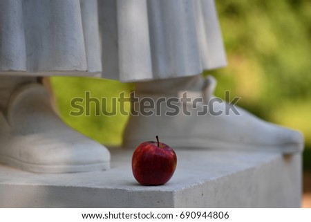 Statue of a poet with an red apple placed on the monument.  #690944806
