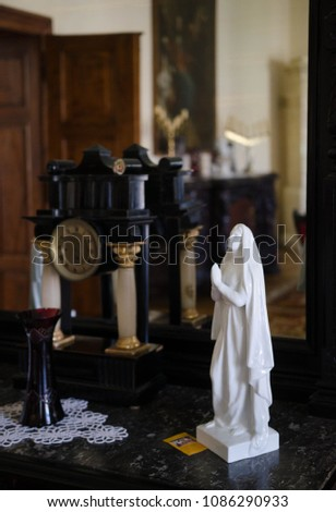 Statue of a saint with antiquities in an interior #1086290933
