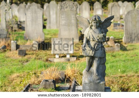 statue of a stone cherubim / angel in a cemetery in london, england