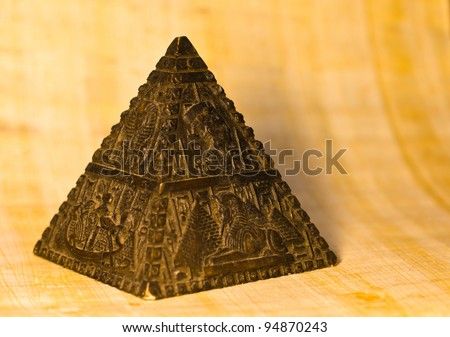 Statue of a stone pyramid with representations of typical egyptian scenes. Papyrus paper background, selective depth of field.