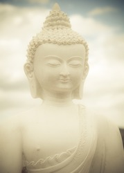 Statue of a white Buddha against clouds and sky