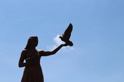 Statue of a woman feeding a bird