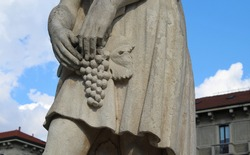 Statue of a woman with a bunch of grapes during the grape harvest