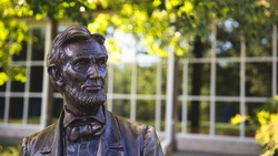 Statue of Abraham Lincoln Sitting With Green Blurry Leaf Bokeh And White Window Frame In Background, Gettysburg Battlefield, Pennsylvania, United State