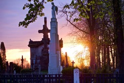 Statue of an angel and silhouettes of crosses and trees against sky at sunset in an old Christian cemetery