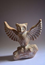 Statue of an owl Infront of a white and grey background
