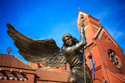 Statue of Archangel Michael with outstretched wings, thrusting a spear into a dragon before the Catholic Church of St. Simon and St. Helena on Independence Square in Minsk, Belarus