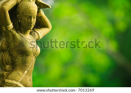Statue of Asian woman against green foliage background