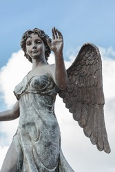 Statue of beautiful angel on white cloud blue sky background