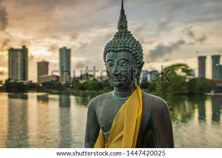 Statue of Buddha made of bronze in a peacefull pose, in front of a cityscape on the Beira Lake in Colombo, Sri Lanka. #1447420025