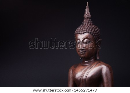 Statue of Buddha made of wood in a peacefull pose, on black background. #1455291479