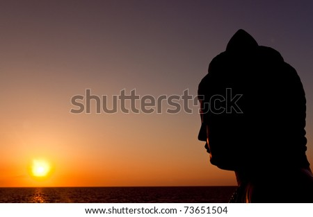 statue of buddha watching sunset over pacific ocean