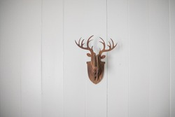 Statue of deer head made from puzzle on white blank wall