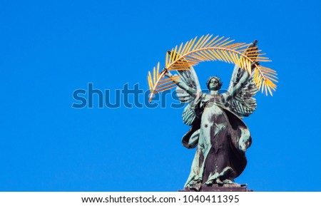 Statue of glory. Facade of the Opera and Ballet Theater. Bronze, Gold (ars longa vita brevis)