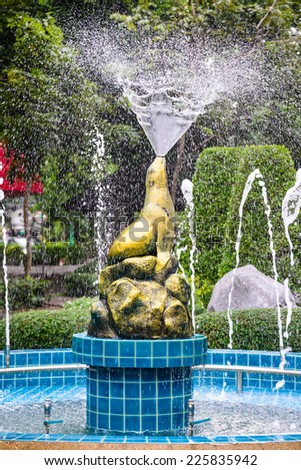 Statue of golden seal sitting blow as fountain.