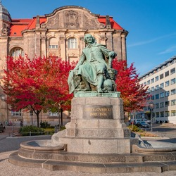 Statue of great scientist Otto von Guericke in red and golden Autumn colors in historical downtown of Magdeburg Germany, at sunny day and blue sky, closeup, details