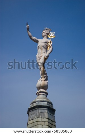 Statue of Hermes the messenger to Greek Gods carrying his golden staff known as a caduceus.  The Romans referred to the god as Mercury. Public statue on a roof in central London for over 100 years.