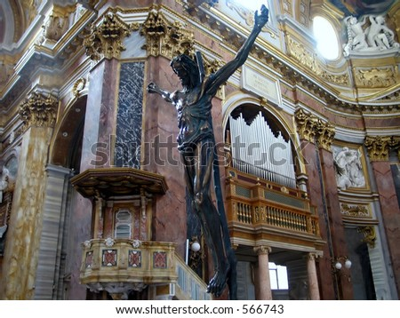 statue of Jesus on a cross with a background of an organ and baroque style roman church andceiling