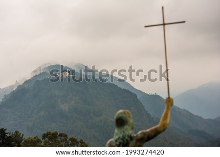 Statue of Jesus on Mount Monserrate holding a cross with mountain and clouds in the background. El Señor Caído Foto stock ©