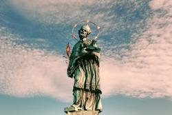 Statue of John of Nepomuk on Charles Bridge in Prague against the sky.