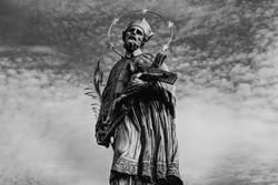 Statue of John of Nepomuk on Charles Bridge in Prague against the sky. Monochrome.