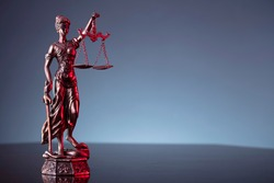Statue of justice on grey background. Red contrast light. Place for text.