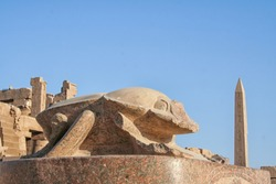 Statue of Khepri the sacred scarab in Karnak Temple Complex (Luxor, Egypt) with obelisk and blue sky in background