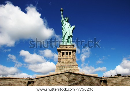Statue Of Liberty against deep blue sky and clouds