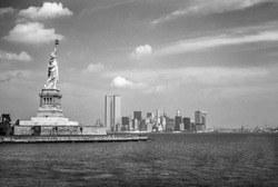 Statue of Liberty and Twin Towers of the World Trade Center. New York City skyline view from the ferry. Black and white background.