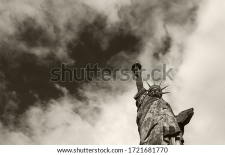 Statue of Liberty at Isle of the Swans in Paris (France) against dramatic sky cloudscape at background. Democracy, freedom, law, struggle concepts. Bottom view. Sepia historic photo. Foto stock ©