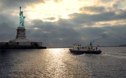 statue of liberty at the sunset and  sailing boat