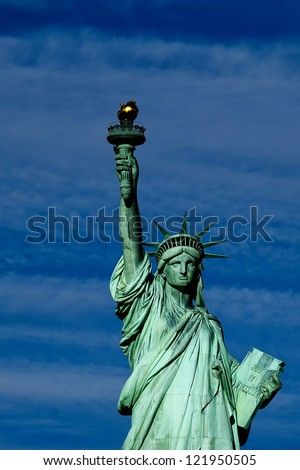Statue of liberty close up vertical isolated in blue cloudy background