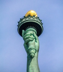 Statue of Liberty: close up view on Lady liberty right hand holds a torch above her head.  NYC . blue sky background
