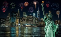 Statue of liberty in front of Manhattan skyline, in Dumbo at night, and fireworks