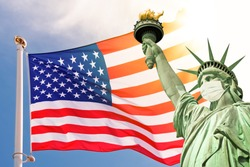 Statue of Liberty wearing a surgical mask, US  american flag background. New coronavirus, covid-19 in New York and USA epidemic crisis concept