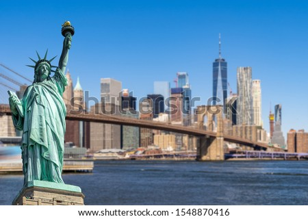 Statue of Liberty with background of Brooklyn bridge and Lower Manhattan skyscrapers bulding for New York City in New York State NY , USA